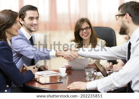 Business group sealing a deal at office - stock photo
