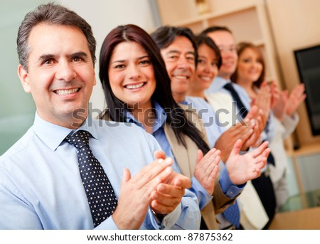 Business group standing in a row and applauding - stock photo