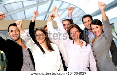 Business group with arms up celebrating their success
