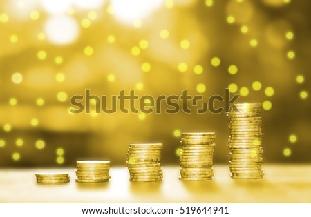 Business growth concept. Money pile coins on wood table with golden filter
