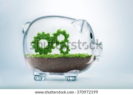 Business growth concept with grass growing in shape of gears inside transparent piggy bank