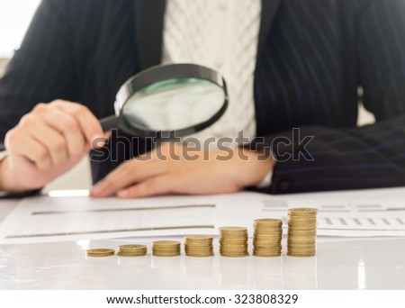 business growth concepts. close-up golden coins with business people using a magnifying glass analysis report. - stock photo