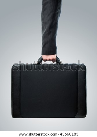 Business Hand and arm holding brief case over a gray radial gradient background - stock photo