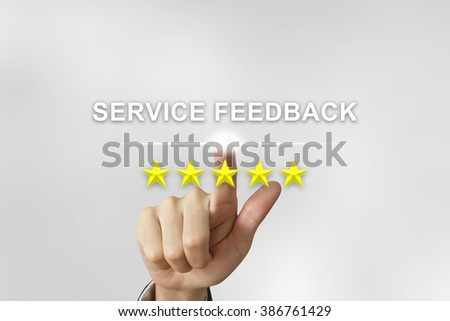 business hand clicking service feedback with five stars on screen - stock photo