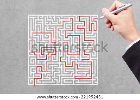 business hand finding solution the maze - stock photo