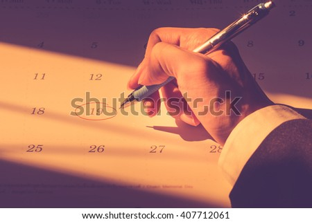 Business hand hold a pen circle the date for important schedule calendar. Tuesday 19 April. Vintage filter tone. - stock photo