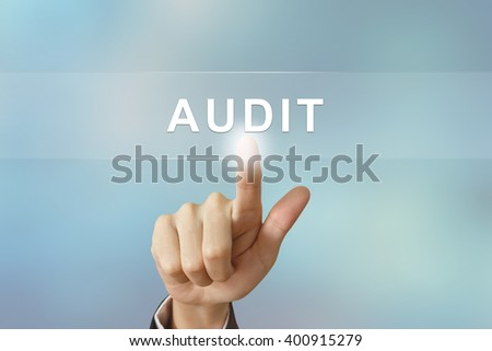 business hand pushing audit button on blurred background - stock photo