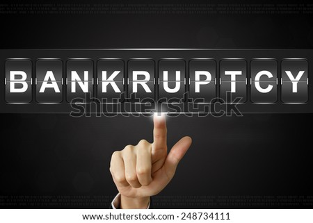 business hand pushing bankruptcy on Flipboard Display - stock photo
