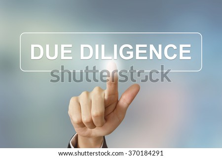 business hand pushing due diligence button on blurred background