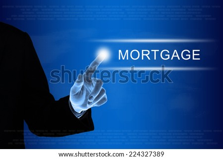 business hand pushing financial mortgage button on a touch screen interface  - stock photo