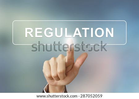 business hand pushing regulation button on blurred background