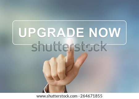 business hand pushing upgrade now button on blurred background - stock photo