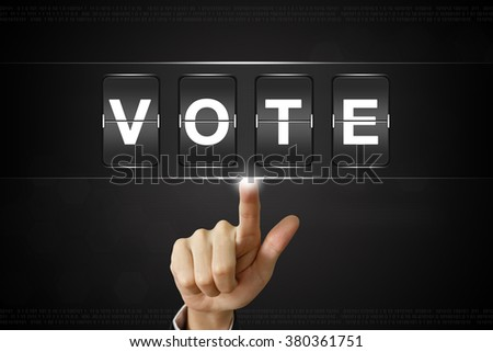 business hand pushing vote on Flipboard Display - stock photo