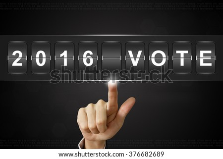 business hand pushing 2016 vote presidential election on Flipboard Display - stock photo