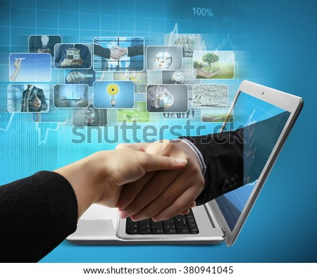 Business  hand reaching out from screen laptop shake Hand from notebook