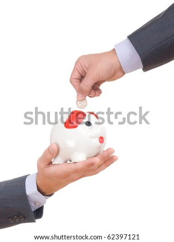Business hand saving money in the piggy bank - stock photo
