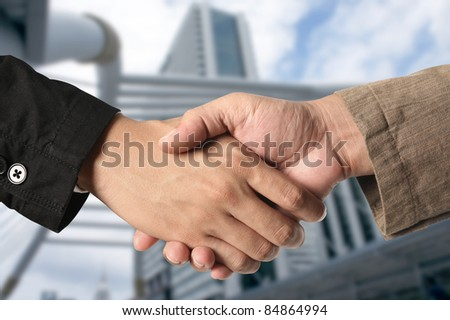 business hand shake and a building in background