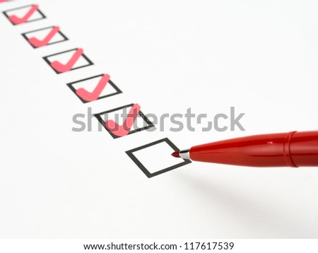 business hand with red pen marking check boxes - stock photo