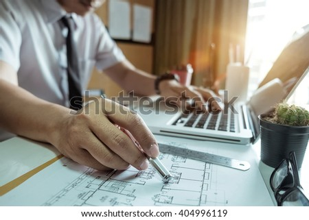 business hand working and smart phone and laptop with  on on architectural project at construction site at office desk in office