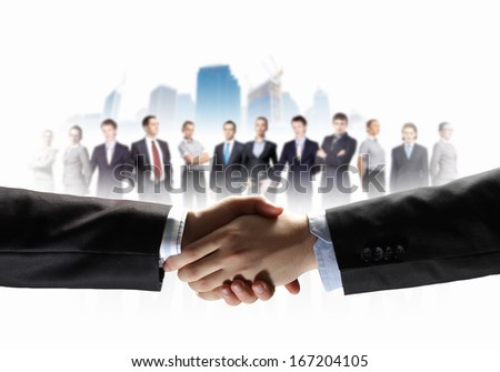 business handshake against white background and standing businesspeople - stock photo
