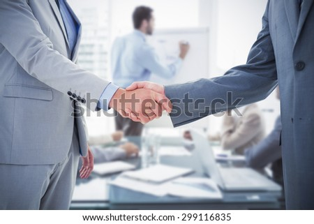 Business handshake against young business people in board room meeting - stock photo