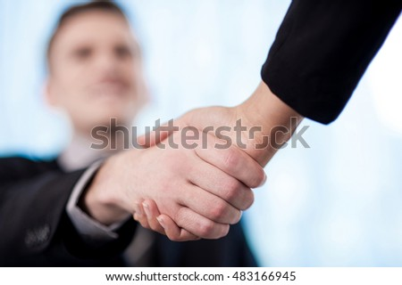 Business handshake among two corporate people - focus concept.