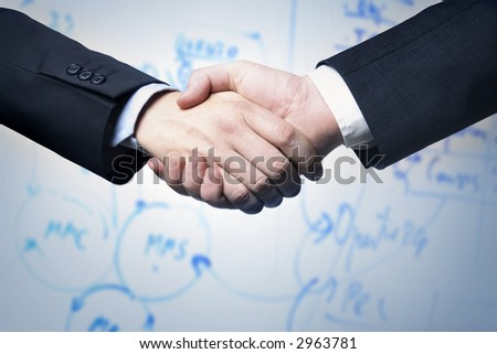 Business handshake and a plan in background