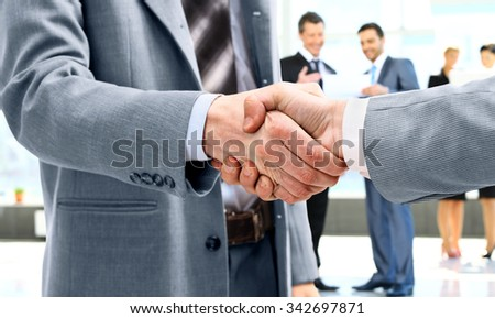 Business handshake and business people - stock photo