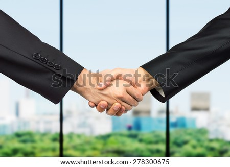 business handshake between partners with city skyline through the window on the background - stock photo