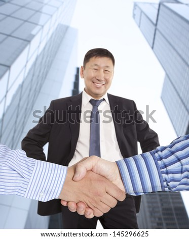 Business handshake between two colleagues on the background of happy asian businessman   - stock photo