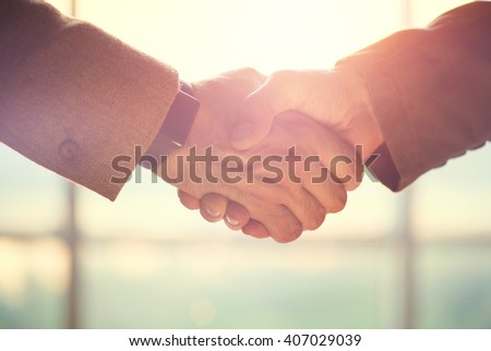 Business handshake. Business handshake and business people concept. Two men shaking hands over sunny office background. Partnership, Deal - stock photo