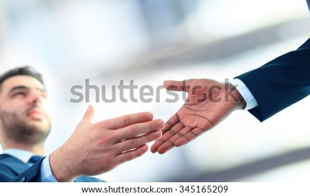 Business handshake. Business man giving a handshake to close the deal  - stock photo
