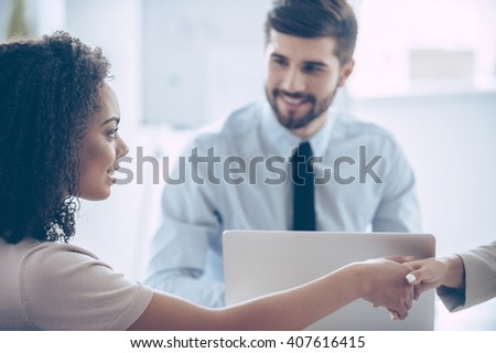 Business handshake. Close-up part of young African women shaking hands with smile while sitting at the office table with her coworkers  - stock photo