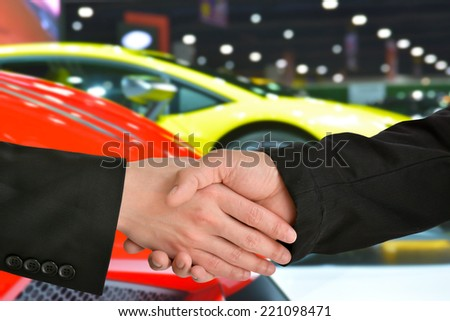 Business handshake closing a deal with car exhibition background  - stock photo