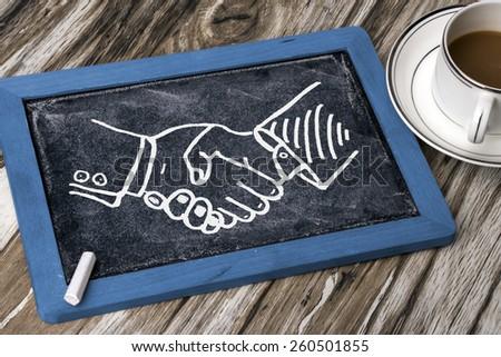 business handshake deal drawn on blackboard - stock photo