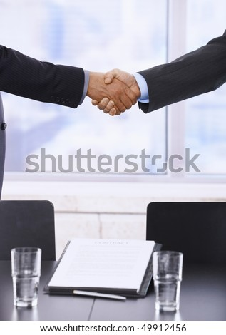 Business handshake in closeup over signed contract.