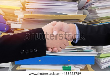 Business handshake in front of documents on desk stack up high waiting to be managed.