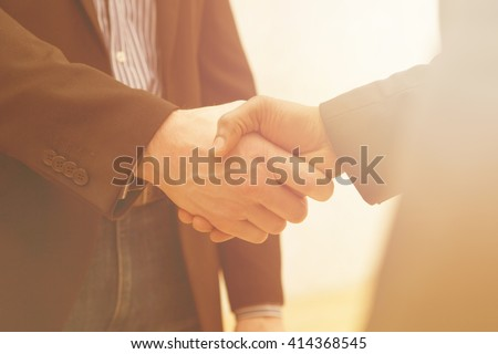 Business handshake of two men demonstrating their agreement to sign agreement or contract between their firms / companies / enterprises. - stock photo