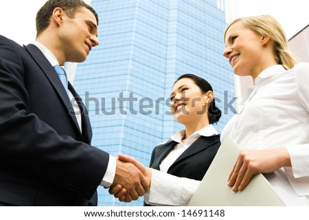 Business handshake of two successful partners at modern building - stock photo