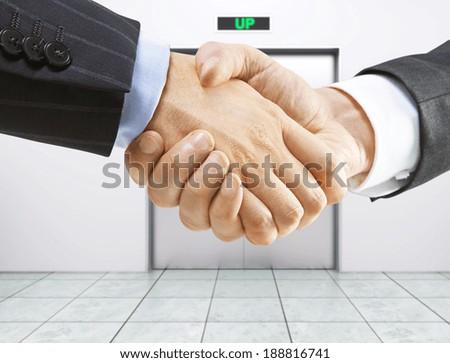 business handshake on a elevator background - stock photo