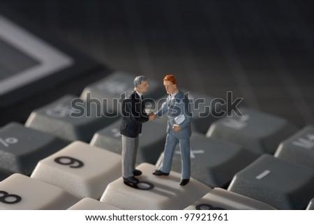Business handshake on calculator concept - stock photo
