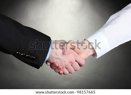 Business handshake on gray background - stock photo