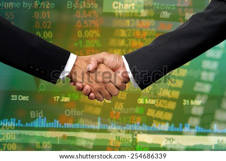Business handshake on stock market background - stock photo