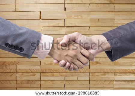 Business handshake on wood background - stock photo