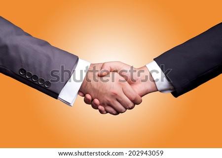 Business handshake orange background - stock photo