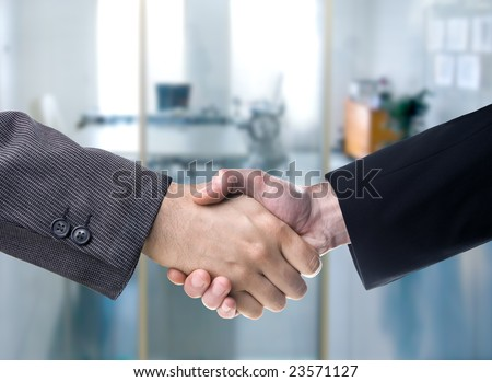 Business handshake over a blurred office background
