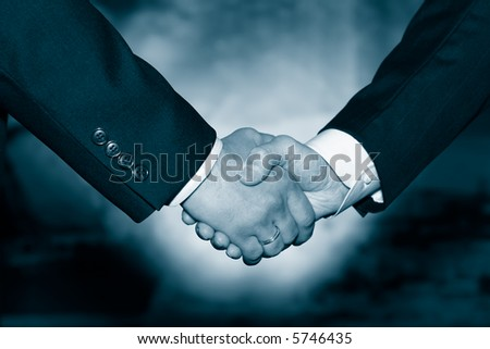 Business handshake over abstract blue background - stock photo
