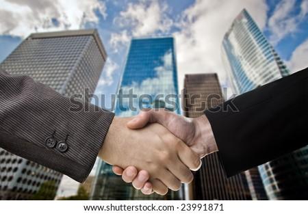 Business handshake over blurred skyscraper background - stock photo