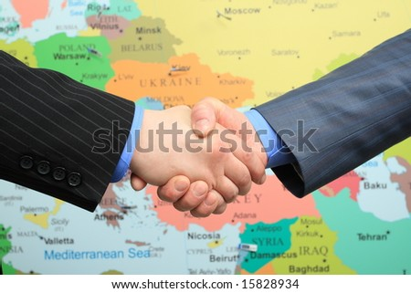 Business handshake over world map background - stock photo