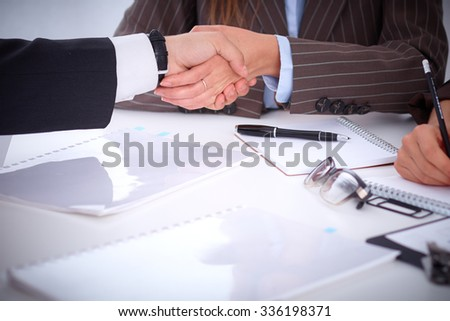 Business handshake  sitting at the desk on office background, copy space area at the left upper corner